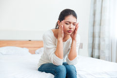 Woman sitting on the bed with headache Royalty Free Stock Photos