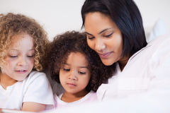 Woman sitting on the bed with her daughters Royalty Free Stock Photos