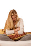 Woman sitting on bed holding belly because of the pain in stomac Stock Images