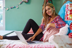 Woman Sitting On Bed At Home Using Digital Laptop Computer Stock Photography