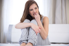 Woman sitting on the bed at home. Worried young woman sitting on the bed at home stock photography