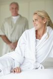 Woman sitting on bed with husband at the back Stock Photos