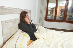 Woman sitting on bed irritated when they hear the alarm clock. E. Arly wake up not getting enough sleep sleeping lifestyle lazy pillow young bedroom rest relax royalty free stock photography