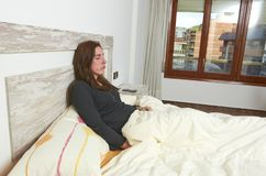 Woman sitting on bed irritated when they hear the alarm clock. E. Arly wake up not getting enough sleep sleeping lifestyle lazy pillow young bedroom rest relax stock photo