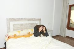 Woman sitting on bed irritated when they hear the alarm clock. E. Arly wake up not getting enough sleep sleeping lifestyle lazy pillow young bedroom rest relax stock photography