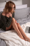 Woman sitting on a bed with laptop, beautiful long legs Royalty Free Stock Photos