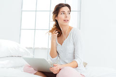 Woman sitting on the bed with laptop computer and headphones Royalty Free Stock Images
