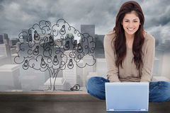 Woman sitting on the bed with the laptop in front of her and smiling Stock Photo