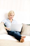 Woman sitting on the bed with laptop Royalty Free Stock Photo