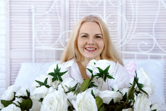 Woman sitting in bed with a large bouquet of roses. Royalty Free Stock Photo