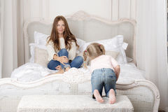Woman sitting on bed and looking at the baby. Girl crawls to her mother Royalty Free Stock Photo