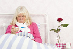 Woman sitting in bed looking at thermometer Royalty Free Stock Photo
