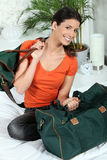 Woman sitting on a bed with luggage Royalty Free Stock Photography