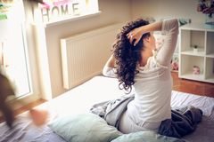 Awaking. Young woman sitting on bed. Woman sitting in bed at morning and stertching. From back stock photography