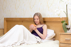 Woman sitting in bed with mug of morning coffee or tea Royalty Free Stock Photos