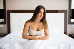 Woman sitting on the bed with pain. Young woman sitting on the bed with pain Royalty Free Stock Photo