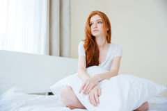 Woman sitting on the bed with pillow Stock Photos