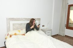 Woman sitting on bed shouting on smartphone after wake up. She l. Ooks crazy sleeping lifestyle lazy pillow young bedroom rest relax person beautiful home pretty royalty free stock images