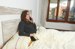 Woman sitting on bed shouting on smartphone after wake up. Woman sitting on bed shouting on smartphone after wake up sleeping happy lifestyle lazy pillow young royalty free stock photos