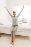 Woman sitting bed stretching Stock Photography
