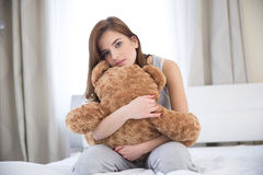 Woman sitting on the bed with teddy bear Stock Image