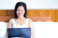 Woman sitting on the bed using her computer. A smiling woman leaning on the bed using her notebook computer Stock Image