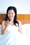 Woman sitting on the bed using her smartphone. A smiling woman leans on the bed using her smartphone Stock Image