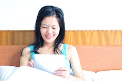 Woman sitting on the bed using her tablet. A smiling woman sitting on the bed using her tablet Royalty Free Stock Photos
