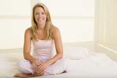 Woman sitting in bedroom smiling royalty free stock photo