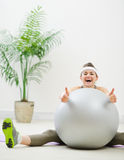 Woman sitting behind ball and showing thumbs up Royalty Free Stock Photos