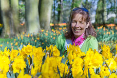 Woman sitting behind daffodils in park Stock Photo