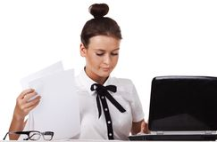 Woman sitting behind a desk through the documents Stock Photography