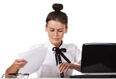 Woman sitting behind a desk through the documents Stock Image