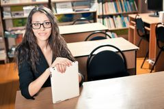 Woman sitting behind the desk at library Stock Photos
