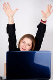 A woman is sitting behind her laptop and is happy Royalty Free Stock Image