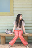 Woman sitting on the bench. Oriental girl sitting on the outdoor bench Stock Photography