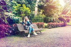 Woman sitting on bench at botanical garden park Stock Photos