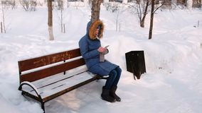 Woman is sitting on bench and browsing mobile phone in winter park in the city during the day in snowy weather with stock video footage