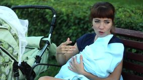 Woman sitting on a bench with a child and grandmother stock footage