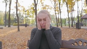 A woman sitting on a bench in a city autumn park is holding her head in her hands, suffering from a headache. A woman sitting on a bench in a city autumn park stock video footage