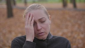 A woman sitting on a bench in a city autumn park is holding her head in her hands, suffering from a headache. A woman sitting on a bench in a city autumn park stock footage