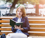 Woman sitting on the bench with diary Stock Image