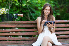 Woman sitting on bench with digital tablet Stock Photos
