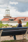 Woman sitting on bench in front of lighthouse Royalty Free Stock Image