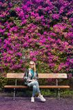 Woman sitting on bench in front of purple flower hedge Royalty Free Stock Photo