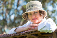 Woman sitting  on a bench in  the garden. Woman in hat  sitting on a wicker bench in the garden Royalty Free Stock Image