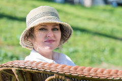 Woman sitting  on a bench in  the garden. Woman in hat sitting on a wicker bench close up Royalty Free Stock Photos