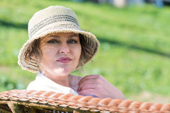 Woman sitting  on a bench in  the garden. Woman in hat  sitting on a wicker bench closeup Royalty Free Stock Photos