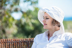 Woman sitting  on a bench in  the garden. Woman in white sitting on a wicker bench and looking away Royalty Free Stock Photography