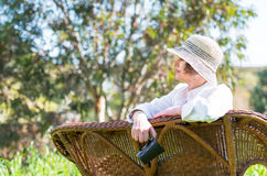 Woman sitting  on a bench in  the garden. Woman in white sitting on a wicker bench and looking away Stock Photos